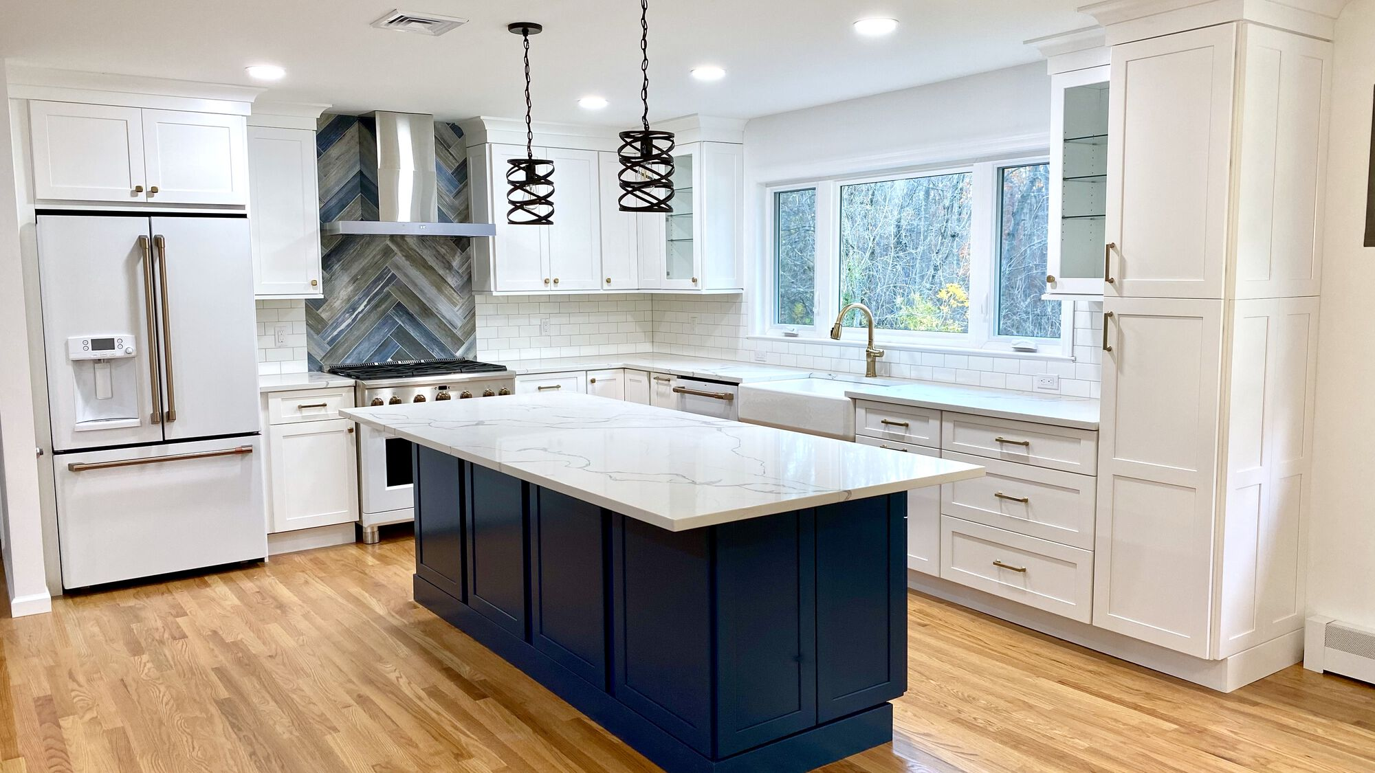 Island in Custom Blue Color, New Window facing Yard with Sink Under, GE Cafe Appliances Matte White Finish, Oak Flooring in Berkeley Heights, Union County NJ