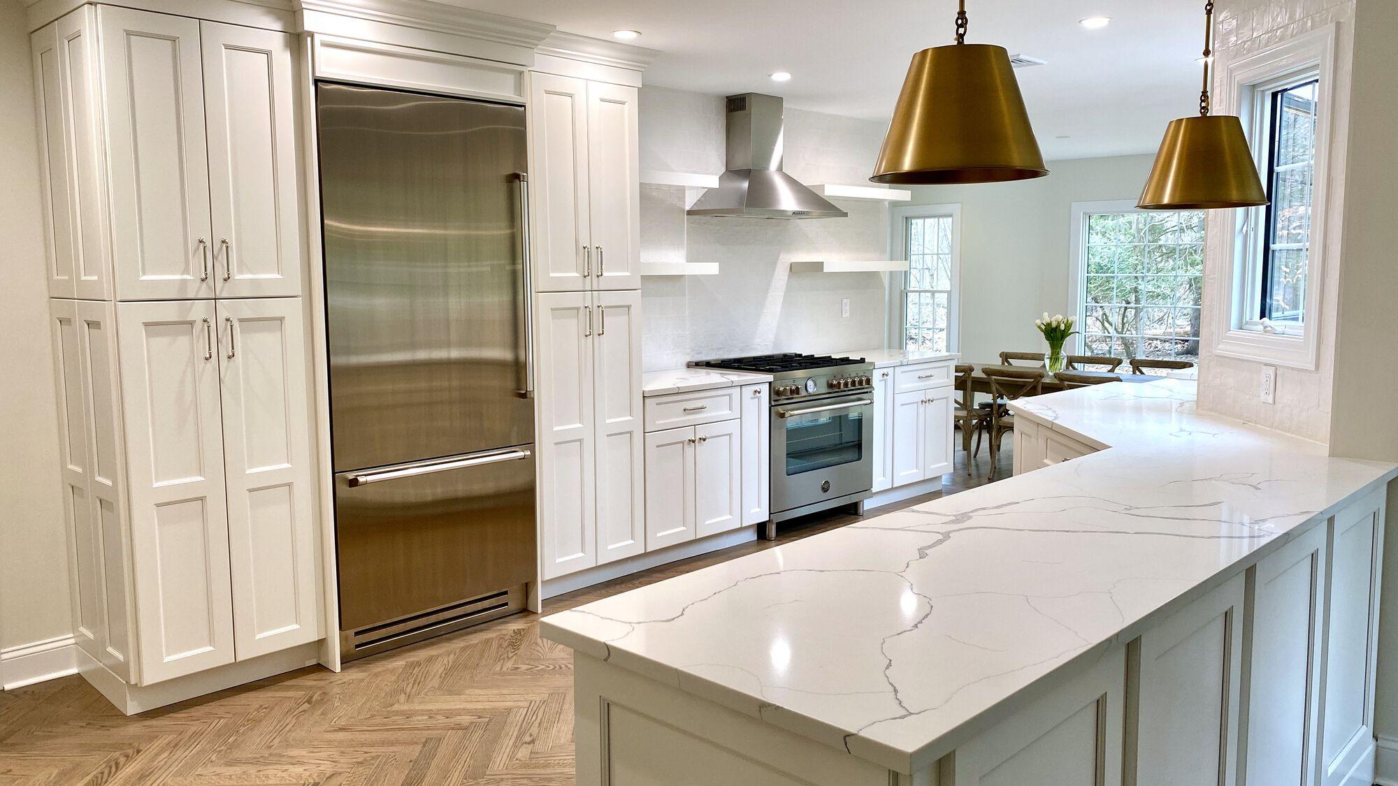 Open Concept Modern Kitchen with White Shaker Cabinetry, Open Shelving, Herringbone Oak Flooring, Calacatta Quartz Counters, Kohler Fixtures, Andersen Windows in Ramsey, Bergen County NJ
